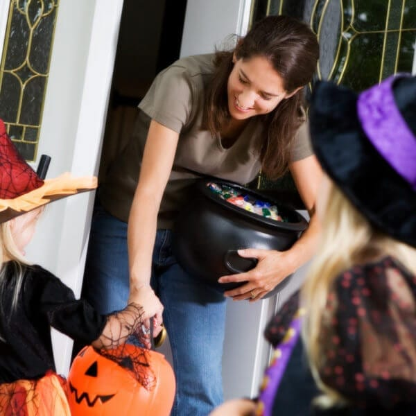 Halloween: Mother Hands Out Candy to Little Girl Witch
