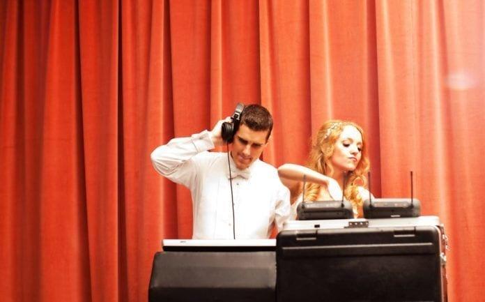 A newlywed couple enjoy DJing music on their wedding day