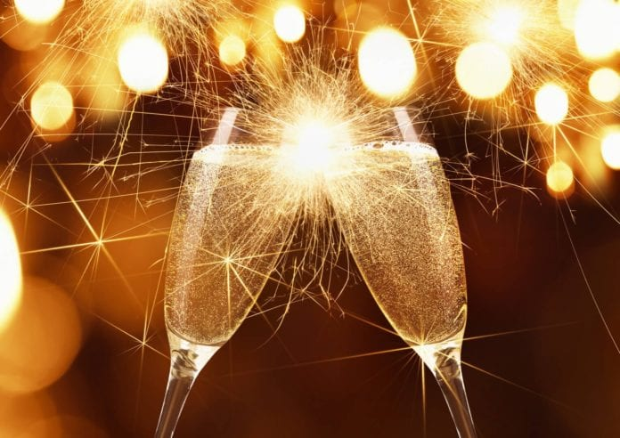 Glasses of champagne and sparklers on bright background with bokeh effect