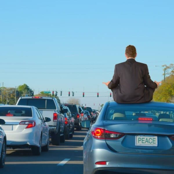 A man is dealing with intense work rush hour traffic jam stress by getting relief doing yoga on top of his car in this humorous scene that shows PEACE on the license plate of the car he is sitting on.