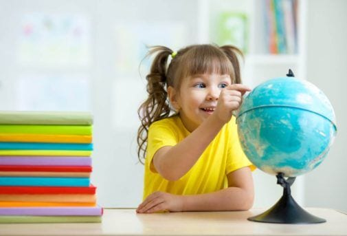 kid girl pointing at globe and sitting at table with books