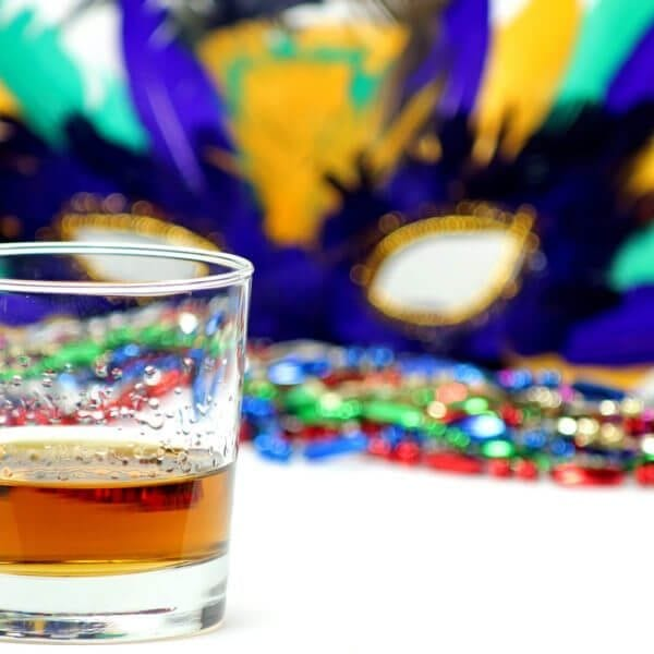 Bourbon in a glass in front of a feathered Mardi Gras mask and beads.