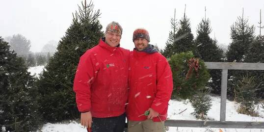 two men in red coats with fir trees