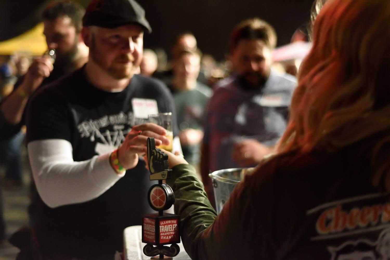 woman handing man a beer