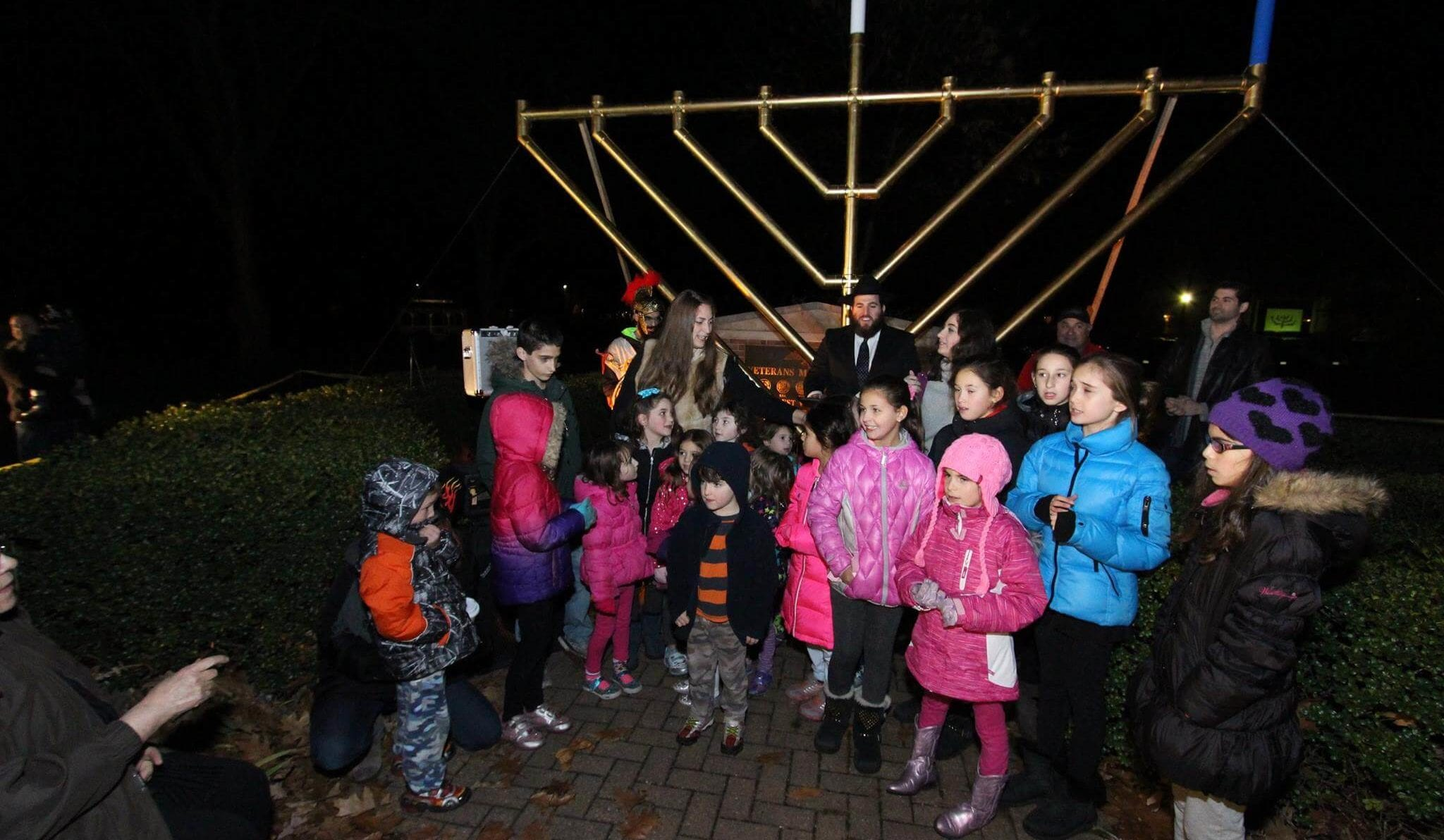 children standing in front of a large menorah
