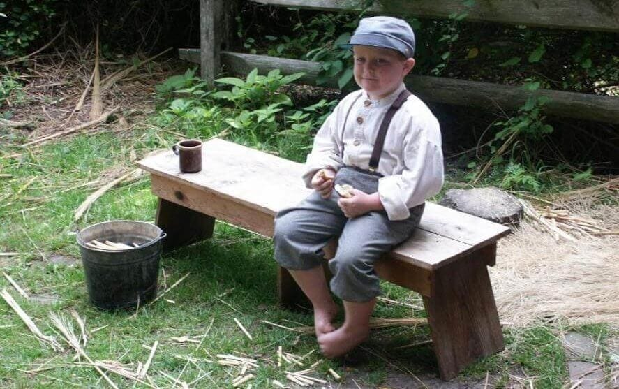 small boy sitting on wood bench whittling