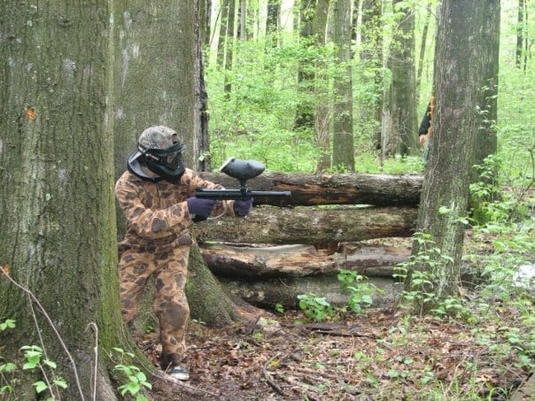 paintball player crouching in woods