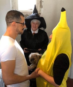 a man, a woman in a banana costume, and a witch officiant at a wedding