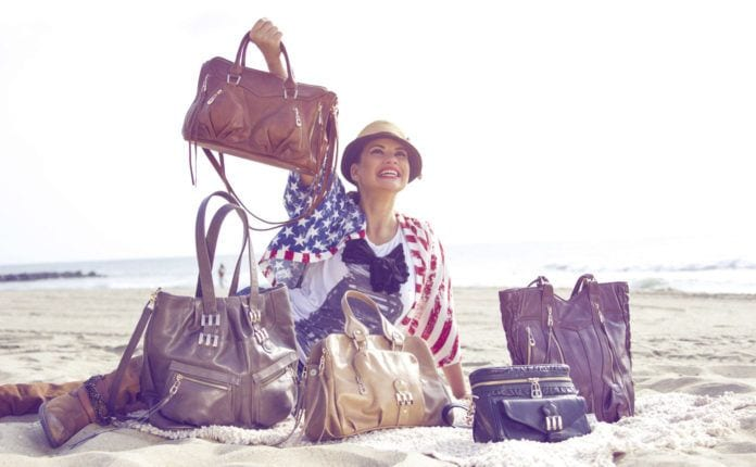 Photo of woman showing off handbags on the beach made by Crystal Kodada