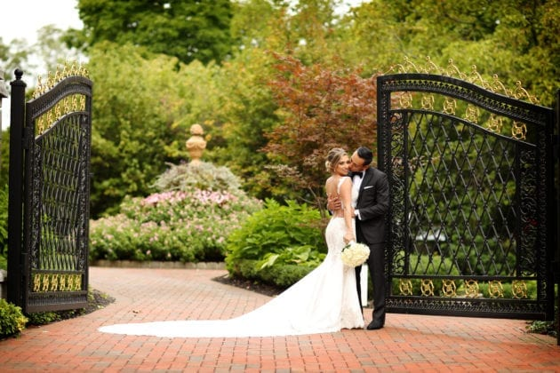 Newlyweds kissing by gate