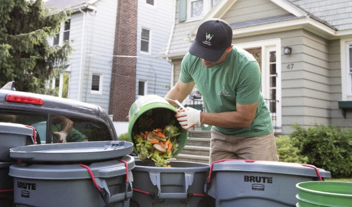Man pouring compost into bin